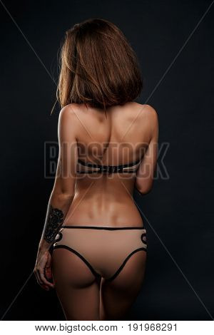 Side view on unrecognizable sexy brunette woman. Nude girl in black erotic lingerie.