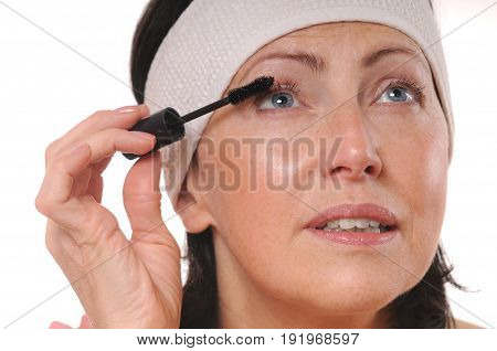 Closeup portrait of mature woman applying mascara on eyelashes. 50-year-old woman put mascara in front of mirror
