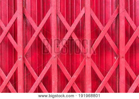 Antique slide steel door locked. Old style of close red steel door. The old Rusty steel door. Folding steel door texture pattern and background. Dark edged.