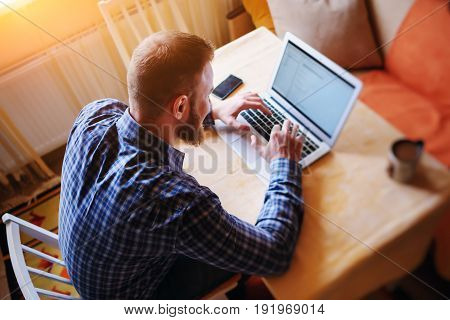 Surfing The Net In Office. Confident Young Man Working On Laptop And Smiling While Sitting At His Wo