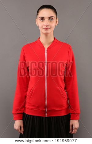 Young hipster girl wearing blank red cotton zip up sweatshirt with copy space for your design or logo mock-up of ltemplate womens hoodie grey wall in the background