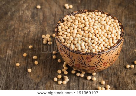 Soybeans in a wooden bowl on the old wood table