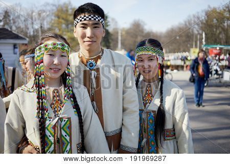 MOSCOW, RUSSIA - APR 29, 2017: Three yakuts people in national folk clothes at Sokolniki park. Sokolniki park is oldest in Moscow and one of the largest in Europe.
