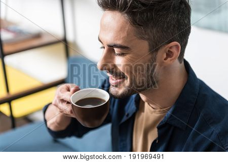Happy young bearded man enjoying his delicious coffee in his room. He is holding cup close to his face with his eyes closed and smelling tasty flavor of beverage. Focus on cup