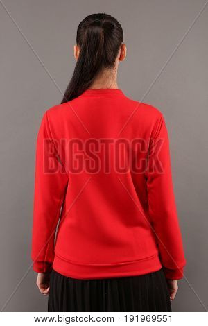 Back of Young hipster girl wearing blank red cotton sweatshirt with copy space for your design or logo mock-up of ltemplate womens hoodie grey wall in the background