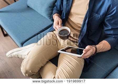 Close up of body of young man sitting cross-legged on sofa. He is holding cup of coffee in one hand and tablet in other hand