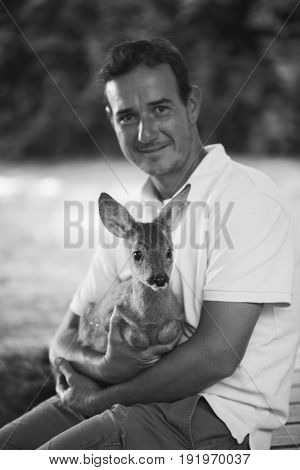 Young zookeeper taking care of young deer fawn