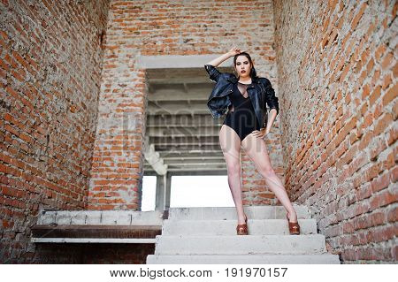 Brunette Plus Size Sexy Woman, Wear At Black One Piece And Leather Jacket, At Abadoned Place.