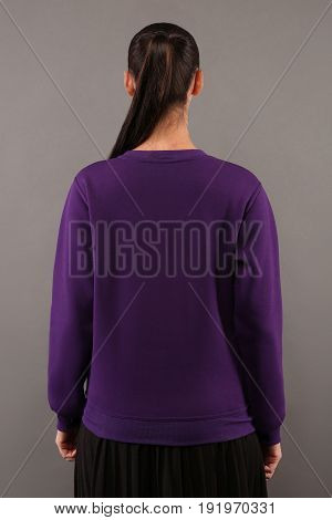 Back of Young hipster girl wearing blank purple cotton sweatshirt with copy space for your design or logo mock-up of purple template womens hoodie grey wall in the background