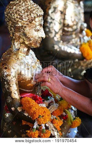 Attach gold leaf on Buddha statue , Buddism make merit by using gold leaf to worship the buddha
