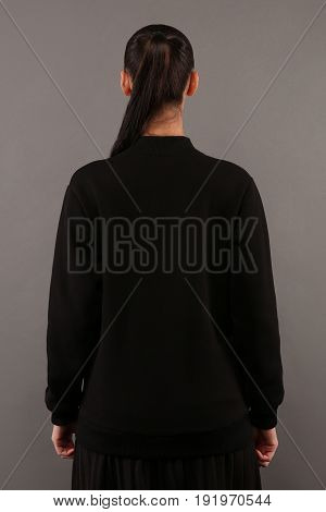 Back of Young hipster girl wearing blank black cotton sweatshirt with copy space for your design or logo mock-up of ltemplate womens hoodie grey wall in the background