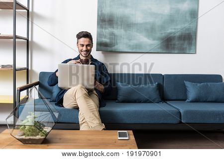 Joyful young bearded guy reading something funny on his laptop computer. He is sitting cross-legged on sofa, holding gadget on laps and drinking coffee. Copy space in right side