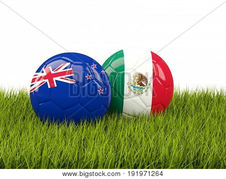 Two Footballs With Flags Of New Zealand And Mexico On Green Grass