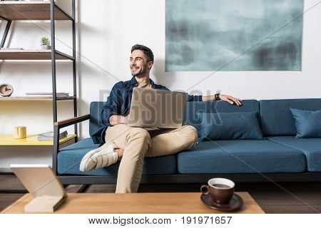 Cheerful young bearded man is sitting relaxed on comfortable couch in his living room with notebook on his laps. He is looking aside with joy and smiling