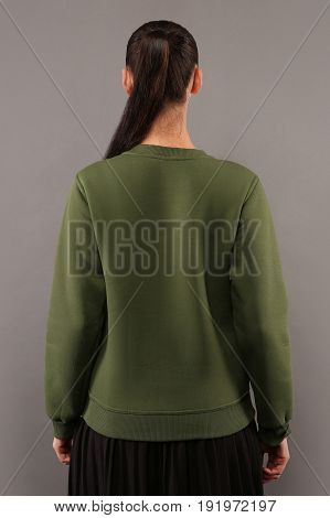 Back of Young hipster girl wearing blank Khaki cotton sweatshirt with copy space for your design or logo mock-up of ltemplate womens hoodie grey wall in the background