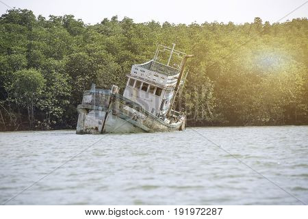 Abandoned boat in golf of Thailand in Phuketsunken wooden transportation boat.