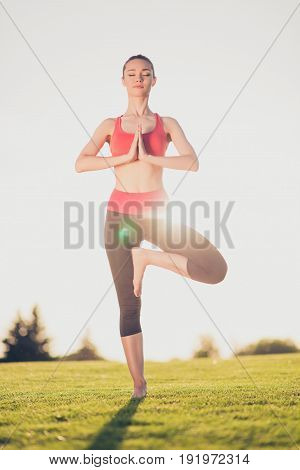 Young Sport Woman Meditates While Practicing Yoga In A Spring Morning Park. Freedom, Calmness, Harmo