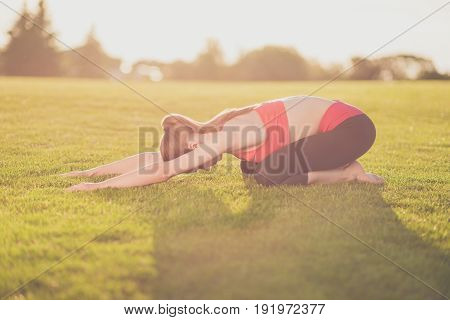 Young Yoga Trainer Is Making Stretching Lying Outdoors In Spring Park On A Nice Green Grass, So Rela