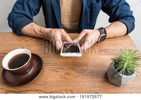 Close up of hands of young man sitting at desk and communicating via mobile phone. Cup of coffee and vase with domestic flower on desktop