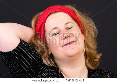 Attractive red haired lite overweight european mature woman with red scarf in hair with closed eyes, relaxed - studio shot on dark background