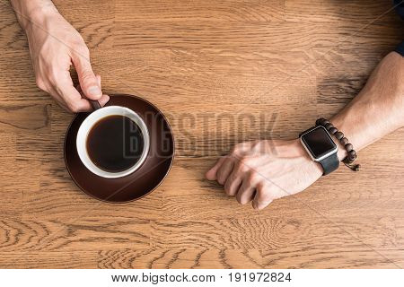 Close up of hands of young man drinking coffee at kitchen table. He is holding cup by its handle by one hand. Top view
