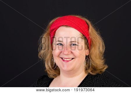 Attractive red haired lite overweight european mature woman with red scarf in hair looking friendly into cam - studio shot on dark background