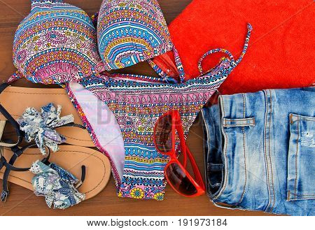 Set of beachwear on wooden background. Red sunglasses towel bikini sandals and jeans shorts. Summer holiday concept