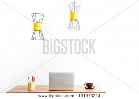 notebook, coffee cup and penholder on desk. Ceiling lamps are hanging over working place. Isolated