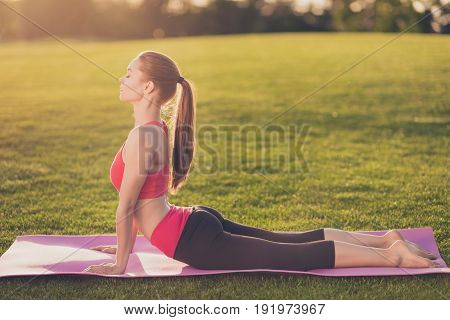 Pretty Young Slim Trainer Is Stretching Her Fit Body. She Is Training Outdoors On A Green Spring Par