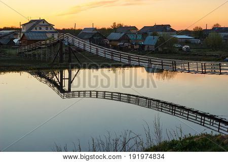 Hanging Wooden Bridge Over The River At Sunset
