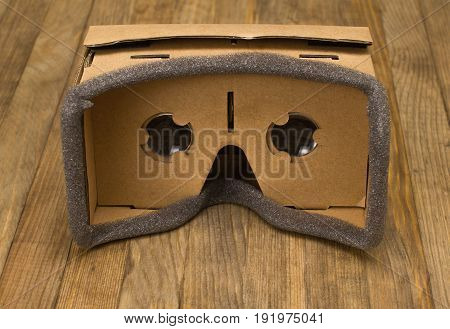 cardboard virtual reality glasses on brown wood front view