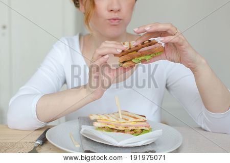 Horizontal indoors crop shot of unrecognizable woman eating sandwich at the table.