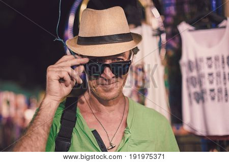 Portrait of a colorful male traveler in a hat and sunglasses. A tourist on the Arambol shopping street in the evening in India a tropical resort. Active holidays in paradise resorts concept travel lifestyle.