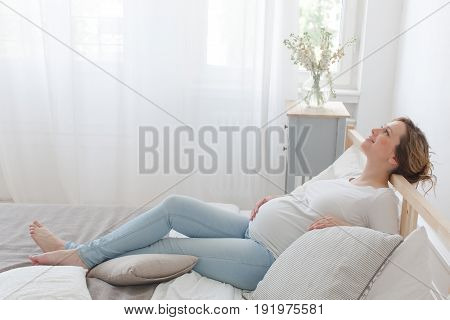 Side view of cheerful pregnant woman touching belly lying on bed.