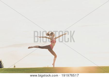 Freedom And Happiness. Young Gymnast In Fashion Sportswear Is Jumping In Graceful Pose On The Sunset