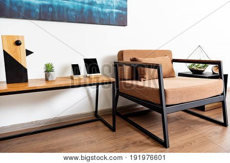 Sunny living room with armchair, drawer unit with flowerpot on it from one side. Long stylish desk with smart phone and tablet on it from other side of comfy chair