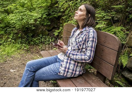 Beautiful woman sitting on a wooden bench in the forest park near the trail holding in his hands a notebook and pencil dreamily staring at the sky.