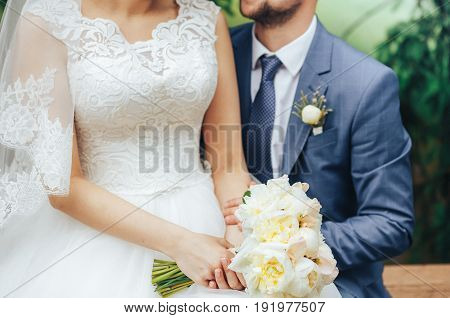 The bride and groom sit side by side and hold a wedding bouquet in their hands