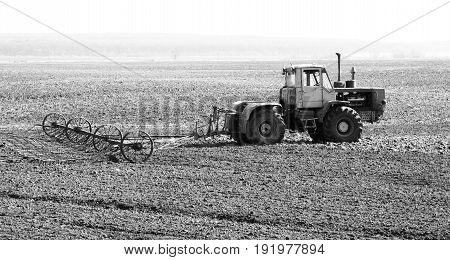 Black-and-white photo of tractor in field in spring