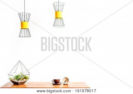 Close up of cup of coffee with round alarm clock and flowerpot on table surface. Lusters hanging over workplace. Isolated and copy space in right side