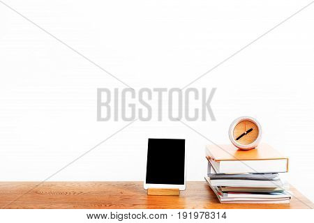 Close up of tablet on holder and pile of notepads with alarm clock on top on table surface. Work concept. Isolated