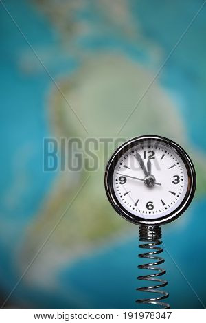 Clock showing 11:56 in front of blurred globe