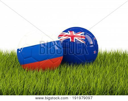 Two Footballs With Flags Of Russia And New Zealand On Green Grass