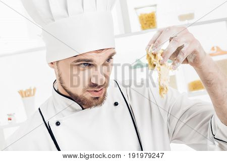 Chef man in uniform makes dough in the kitchen. Bad dough