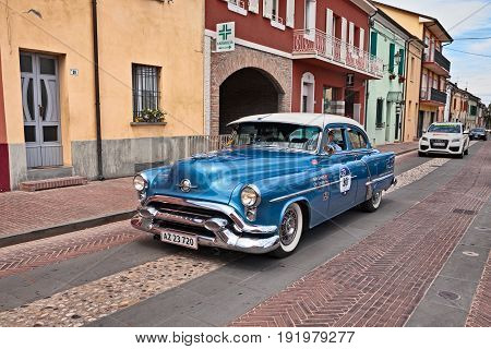 GATTEO, FC, ITALY - MAY 19: driver and co-driver on a vintage American car Oldsmobile 88 (1953) in historical classic car race Mille Miglia, on May 19, 2017 in Gatteo, FC, Italy