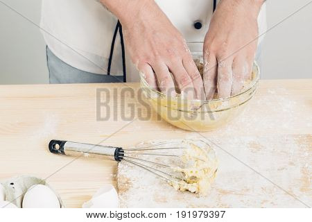 Chef man in uniform kneading raw dough in the kitchen