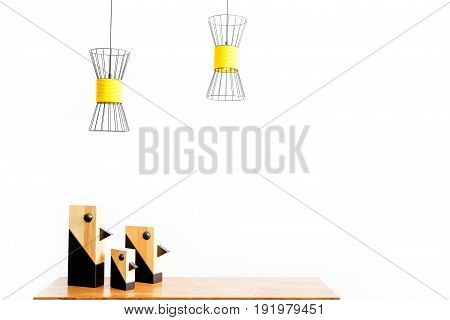 Close up of three different size decorative birds on desktop with chandeliers hanging over workplace. Isolated. Copy space in right side