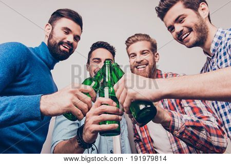 Cheers Men! Bachelor Men`s Life. Low Angle Photo Of Four Happy Friends, Clinking Their Glasses Of Be