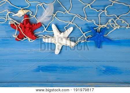 red white and blue starfish in nautical netting with seashell and bird feather on rustic wood
