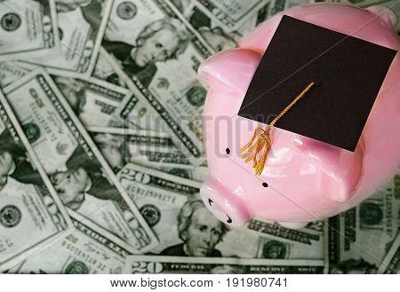 piggy bank with graduation cap on cash